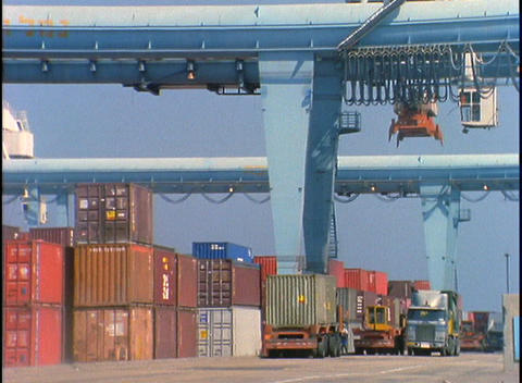 Trucks pass by a huge crane moving cargo at a port Stock Video Footage
