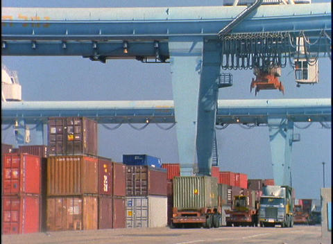 Trucks pass by a huge crane moving cargo at a port Footage