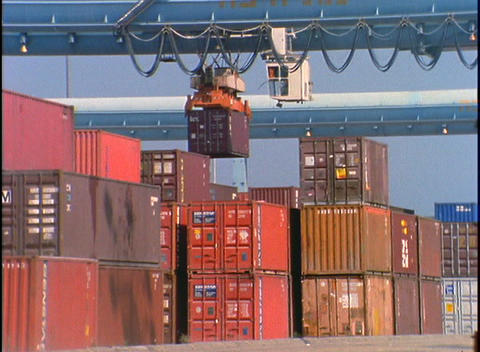 A crane at a port facility lifts large containers Footage
