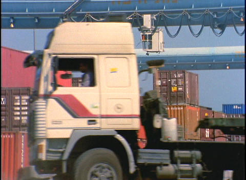 A crane at a port facility lifts large containers Stock Video Footage
