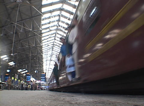 Trains leave the Mumbai Victoria train station Stock Video Footage