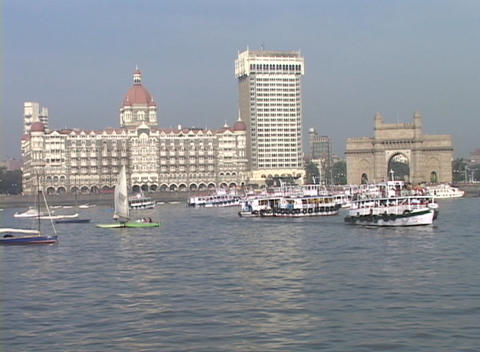 Boats enter and exit the harbor with the Taj Mahal Hotel in the background in Bombay Footage