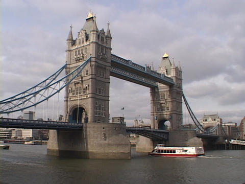 A ferry boat passes under the London Tower Bridge in London, England Footage