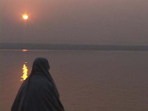With a low sun in the distance, a pilgrim prays near the Ganges River, India Footage