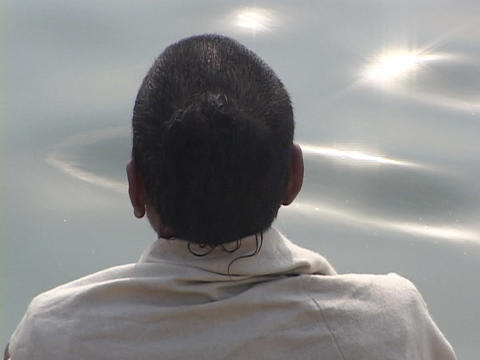 A Hindu pilgrim contemplates by the side of sparkling water Stock Video Footage