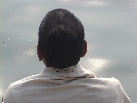 A Hindu pilgrim contemplates by the side of sparkling water Footage