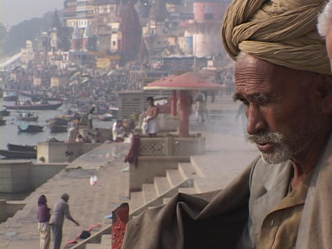 An Indian mystic, also known as a wise man or guru, sits beside gnats in Varanasi, India Footage