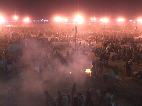 A large refugee camp is lit by spotlights and campfires at night in India Footage