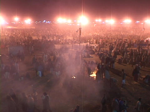 A large refugee camp is lit by spotlights and campfires... Stock Video Footage