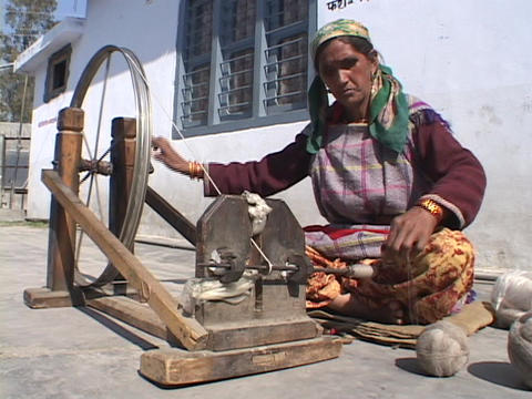 An old woman spins yarn onto a wheel Live Action