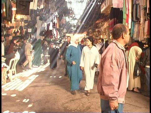 Pedestrians walk through a covered bazaar in Marrakesh,... Stock Video Footage