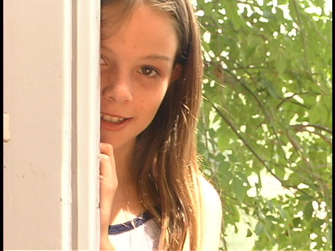 A girl looks out from behind a post Stock Video Footage