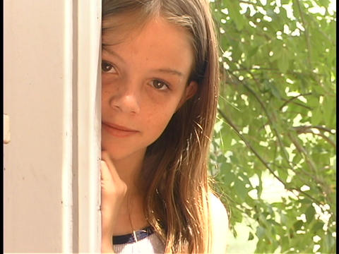 A girl looks out from behind a post Footage