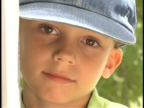 A young boy looks out from behind a post Stock Video Footage