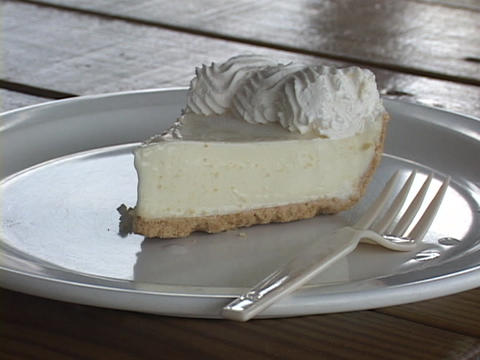 A slice of banana cream pie rests on a plate with a fork Footage