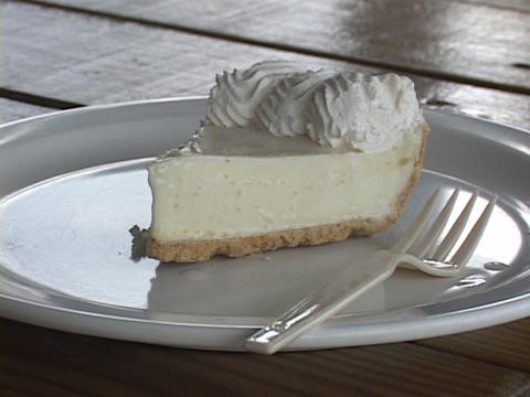 A slice of banana cream pie rests on a plate with a fork Stock Video Footage