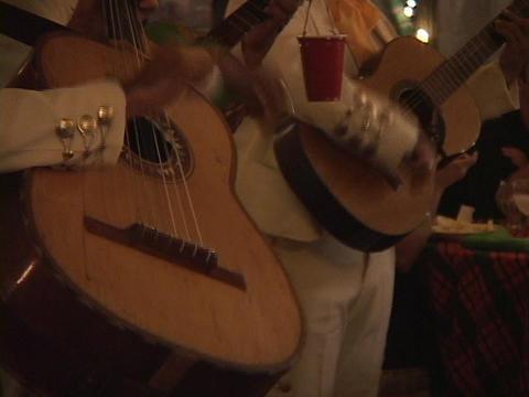 A mariachi band strums their rhythmic guitar music in a restaurant Footage