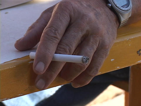 An Old Man's Hand Holds A Burning Cigarette stock footage