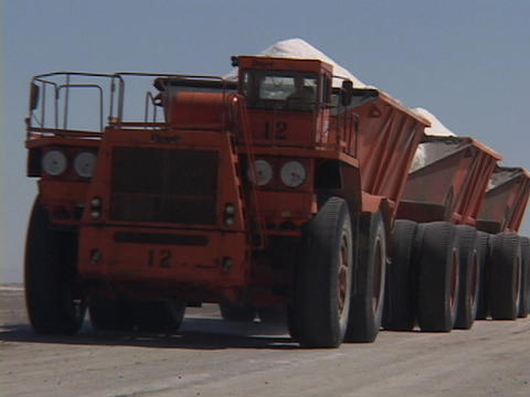 A large salt farm truck carries its' load in three peaked... Stock Video Footage