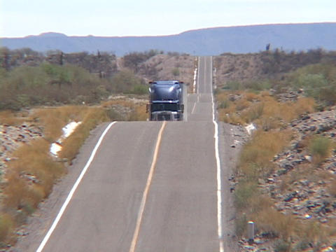 A semi truck traverses a hilly desert road Stock Video Footage