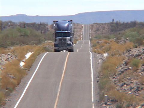 A semi truck traverses a hilly desert road Footage