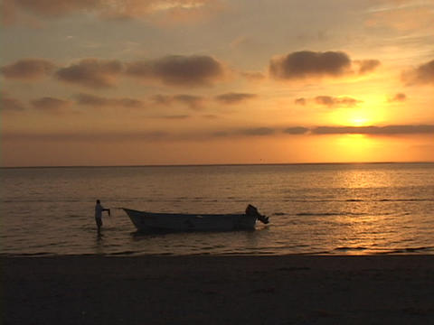 A fisherman pulls a small boat to shore during golden hour Stock Video Footage