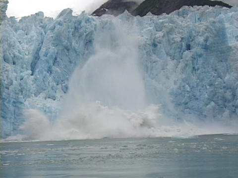 A large chunk of blue iceberg falls into the ocean Footage