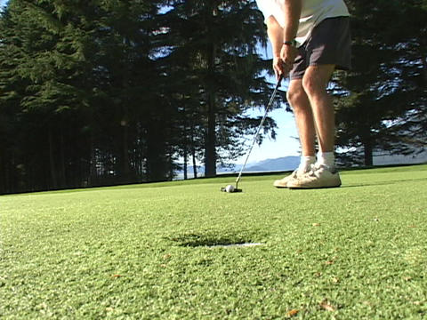 A man putts and the ball goes into the hole Stock Video Footage