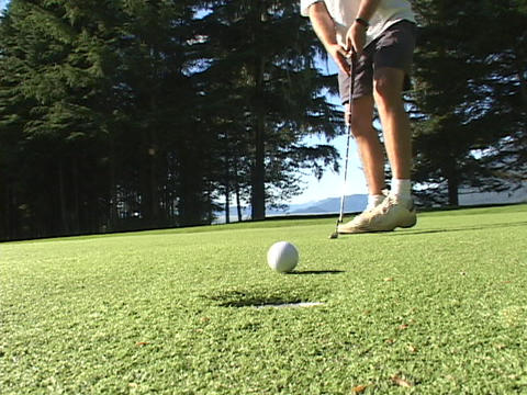 A man putts and the ball goes into the hole Footage
