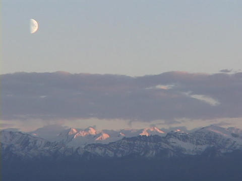 A half moon hangs above purple snow capped mountains at... Stock Video Footage