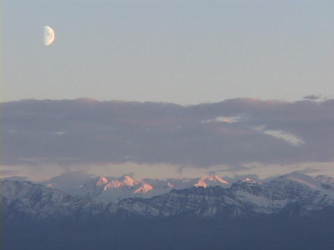 A half moon hangs above purple snow capped mountains at golden hour Footage