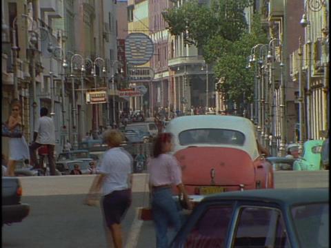 Pedestrians walk among the traffic in downtown Havana, Cuba Stock Video Footage