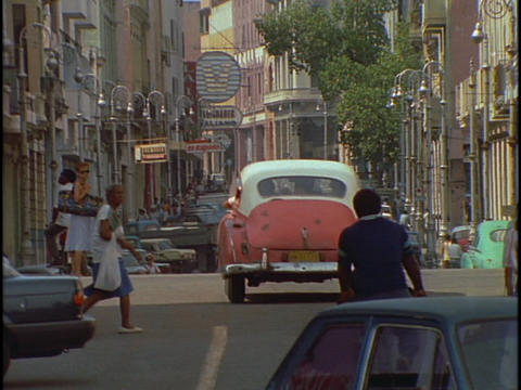 Pedestrians walk among the traffic in downtown Havana, Cuba Footage