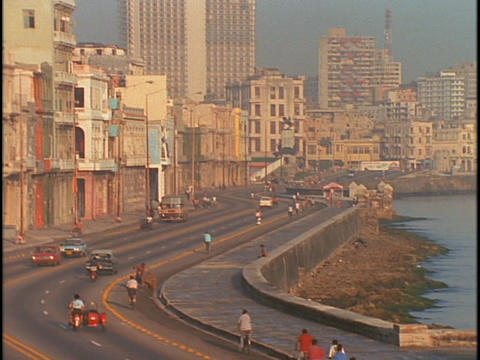 Bicyclists and vehicles travel along the waterfront in Havana, Cuba Footage