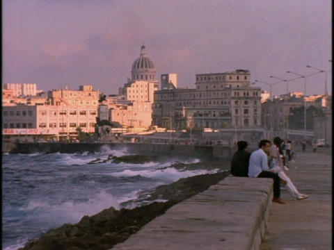 Cuban men sit at the waterfront in Havana Cuba during golden hour Footage
