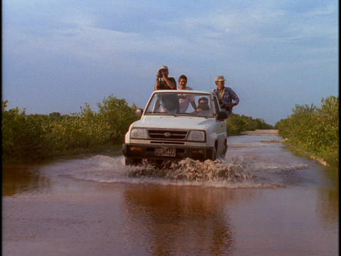 Tourists ride in the back of a jeep through a flooded area Live Action