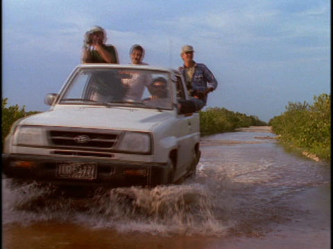 Tourists ride in the back of a jeep through a flooded area Stock Video Footage