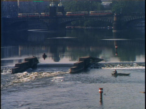 Trains pass on a bridge over a lake with a spillway Stock Video Footage