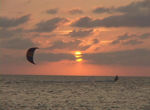 A windsurfer cuts across the water in silhouette against... Stock Video Footage