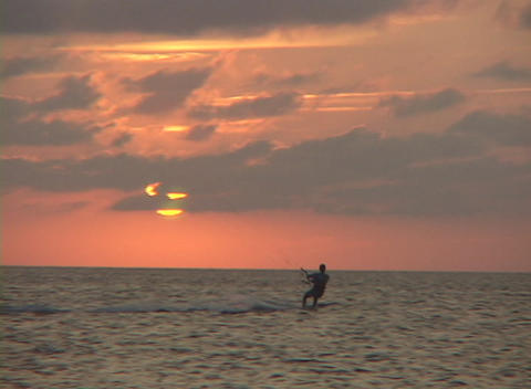 A windsurfer cuts across the water in silhouette against an orange sun Footage