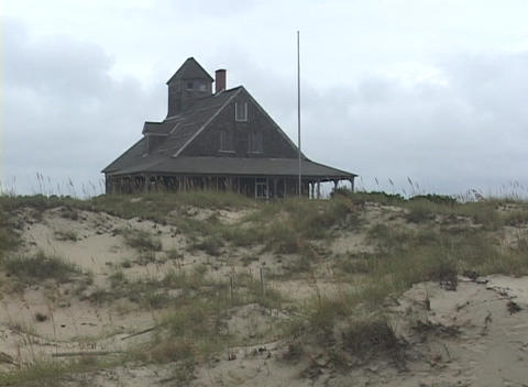 A black beach house rests at the top of a sandy hill Footage