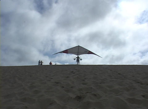 A hang-glider runs and flies out of sight after a successful take-off Footage