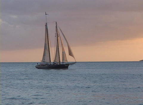 A large sailboat slowly sails across the ocean against a... Stock Video Footage