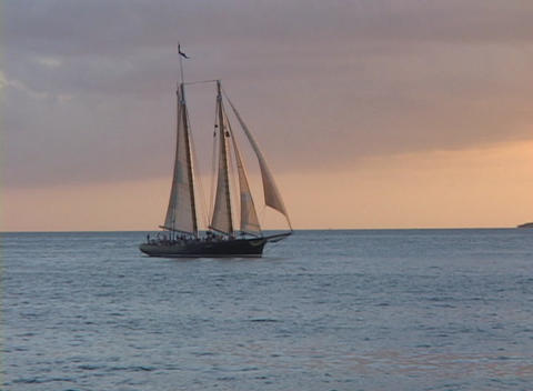 A large sailboat slowly sails across the ocean against a cloudy pink sky Footage
