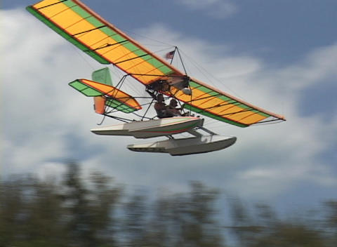 An ultralight airplane makes a smooth landing on the water Footage