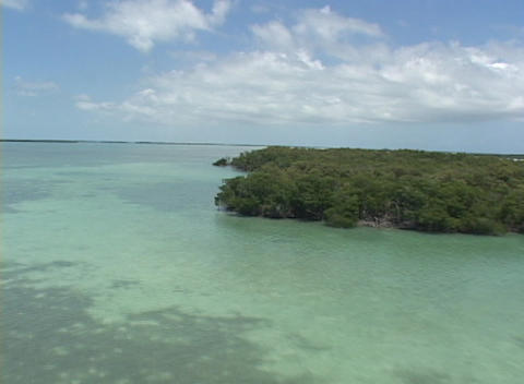 An ultralight airplane flies over an island in the ocean Stock Video Footage