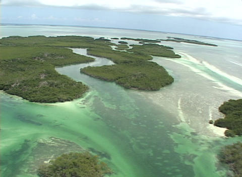 An ultralight airplane flies over some small islands in the ocean Footage