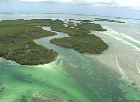 An ultralight airplane flies over some small islands in... Stock Video Footage
