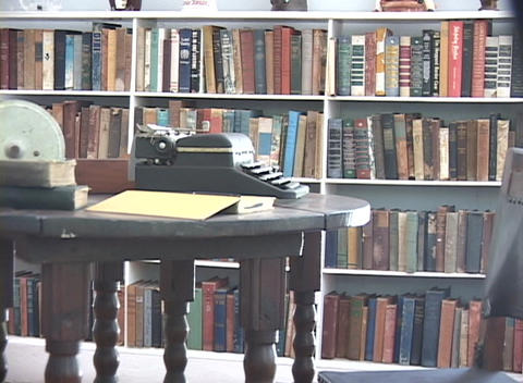 An antique typewriter sits on a table in a library Footage