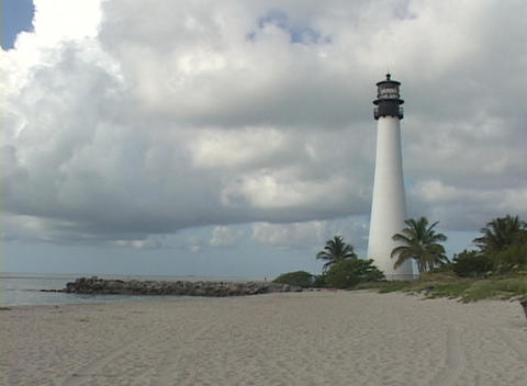 A lighthouse stands at the edge of a beach Stock Video Footage